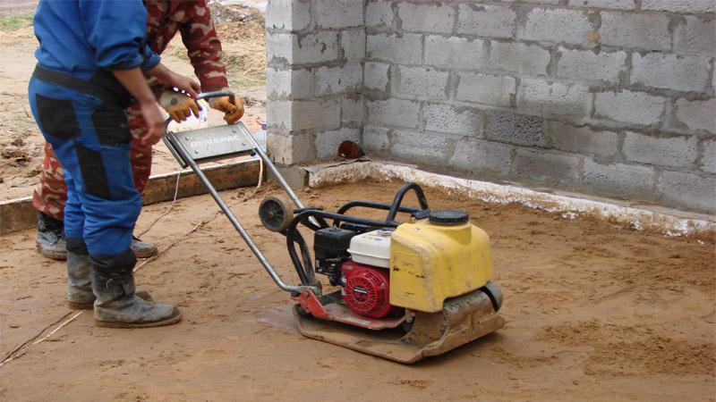 Трамбовка песчаного слоя бетонного пола